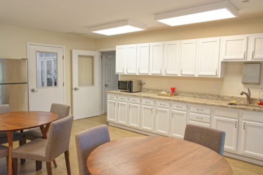 Communal dining room with fridge, microwave, sink, cabinets and seating