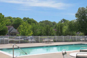 Fenced in swimming pool, seating with tables and trees