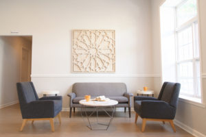 Bright lounge room with tables, couch and chairs